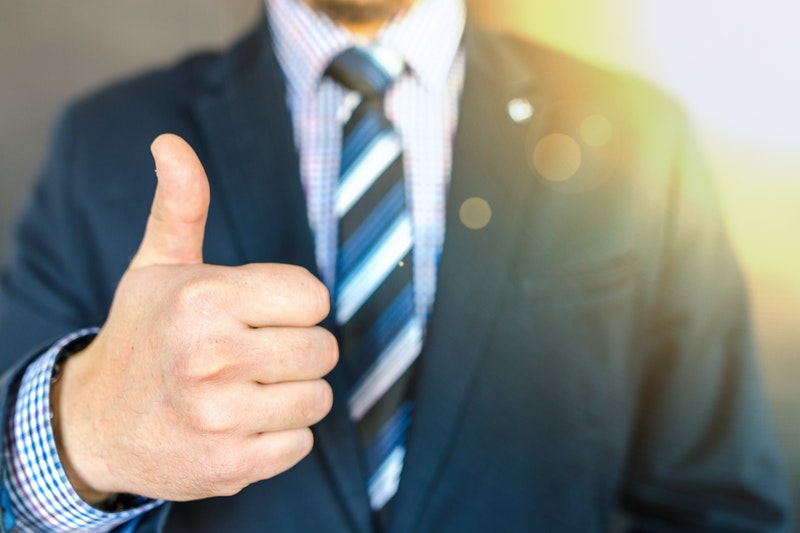 close up photo of man in suit showing a thumbs up, why hire a digital marketing specialist, digital marketing